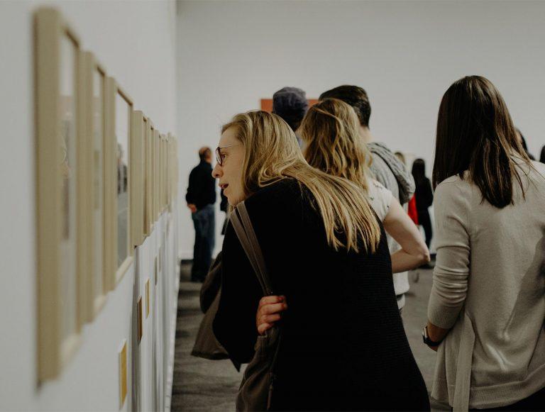 Woman, arms folded, peering at wall of artwork