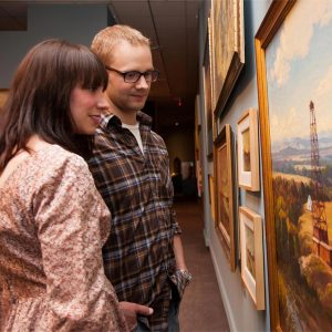 Man and woman appreciating a wall of paintings