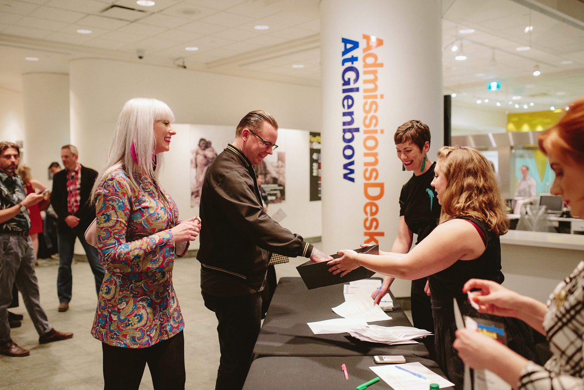 Staff assist guests in Glenbow lobby