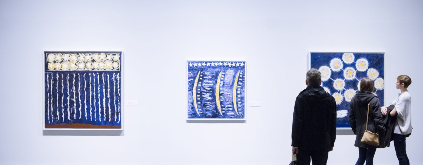 Three people looking at three large blue pieces of art