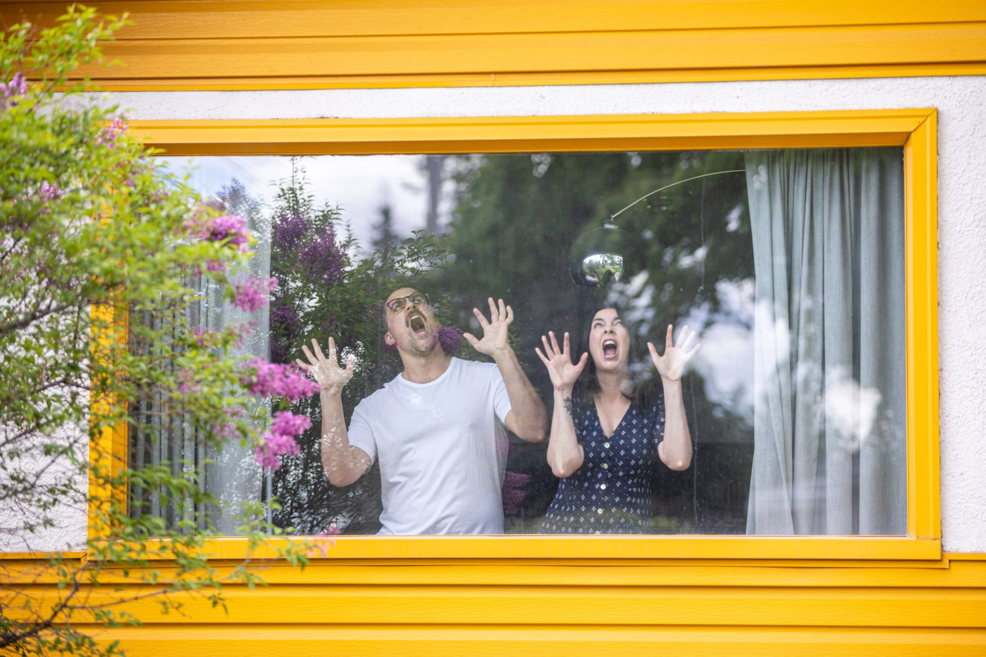 A portrait of a man and a woman making faces while looking out the window of their house